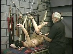 Brunette innocent suspended like a gymnast in dungeon