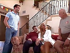 Blonda cougar med stora tuttar rider en ung kuk på en soffa medan make klockor