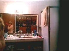 Blonde Babe macht sich bereit für ein Bett, das sich in einem Badezimmer niederschlägt und Voyeur auf sie ausspioniert