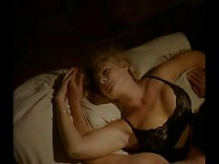 Shannon Tweed in some black lingerie making out wit a guy