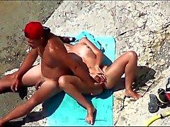 Couple att ömsesidigt onanerar av orgasm hos allmänna stranden