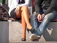 muchacha que se sienta con patas sexy en minifalda