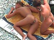 Mädchen mit dem Plug im Arsch posiert für ein Mann am öffentlichen Strand entfernt