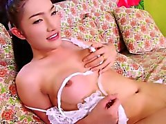 Thai ladyboy Tonlew grips her erect dick masturbating gently