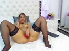 Eine junge Brünette masturbiert vor der Kamera.