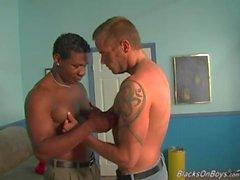 Muskulöser weißer Mann, der von schwarzen Schlägern geteilt wird