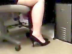 Graziosa pulcino di asiatici sits gambe incrociate alla scrivania a esibisce