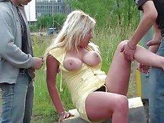 Rondborstige mooi meisje in groep seks in het openbaar
