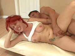Rote Kopf junge Babe saugt und fickt heißen saftigen Schwanz auf dem Sofa
