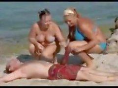 L'uomo con una gallo gigantesca sulla spiaggia fa delle donne parole