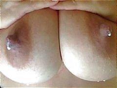 Busty brunett visar hennes stora tuttar till kameran och mjölkar dem