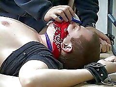 Een vastgebonden man met een prop in zijn mond gaat slecht worden geneukt