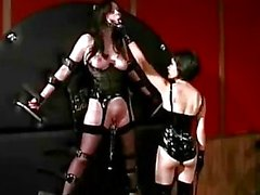 Busty Girl In Corset Tied To Wall Tortured With Clips Spanked With Stick By Mistress In The Dungeon
