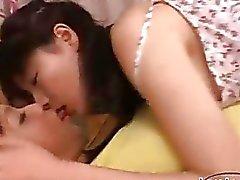 2 Asiatisk flickor kyssa Att suga varje annan Nipples på sängen i rummet