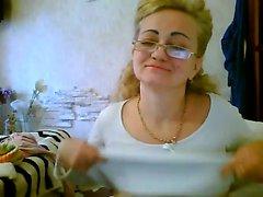 Stygga mogen kvinna som med glasögon exponerar sina stora Tuttar för ton
