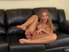 Busty babe Nicole Aniston sits on the couch toying her love hole