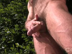 Aaron Cage strokes his dick in the garden, under the sun.