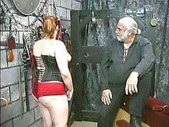 Jonge bdsm slavin brunette in korset is afgedroogd en caned in kelder