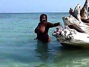 Grasso bambino nero guada naked nelle acque basse e gioca con il ore