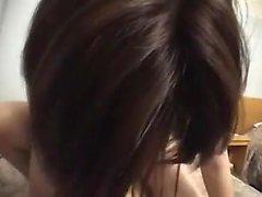 Menina asiática encantadora com belos seios goza de uma porra de disco na cama