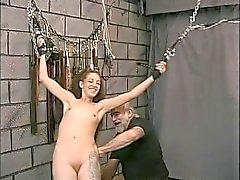 Bondaged slim a-cup brunette in face mask groped by bdsm master