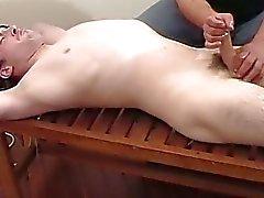 Een kerel wanking uit een vastgebonden jongens pik