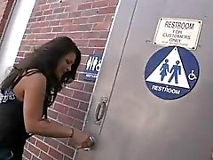 Prachtige brunette zuigt vlezige glory hole pik in het openbaar toilet