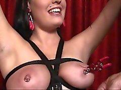 Slampa i läder älskar att vara fastspända och med hennes bröstvårtor fastklämda