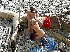Os pares têm o sexo na praia pública, enquanto cara relógios.