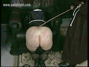 Frecher Nonne mit ihren Rock ist kniend für Master Priesters und verlor mit einem Holzstock auf ihrem gut geformt Esel versohlt