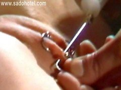 Master is piercing tight pussy lips of hot and horny slave and put metal rings through them