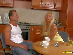 Blonde Candy plays with a hard rod in kitchen